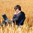 Young successful businessman works in field on notebook — Stock Photo
