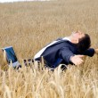 Young businessman takes a rest in field — Stock Photo
