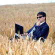 Thoughtful young businessman in field — Stock Photo