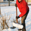 Adult man clean owns yard against snow - Stock Photo