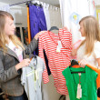 Pretty girls pick out clothes to buy — Stock Photo