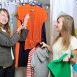 Seller offers to a girl a blouse — Stock Photo #8888406