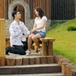 Happy young beautiful smiling couple outdoors sitting on bench — Stock Photo