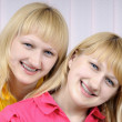 Portrait of two beautiful smiling blond sisters — Stock Photo #8888903