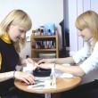 Two beautiful blond girls making manicure - Stock Photo