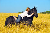 Beautiful woman rides and pets horse in field — Stock Photo