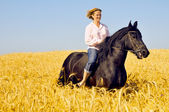 Beautiful smiling woman rides a pretty horse in field — Stock Photo