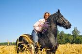 Gülümseyen güzel kadın alanında oldukça siyah ata biniyor — Stok fotoğraf