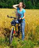 Beautiful smiling girl on bicycle near the golden field — Foto de Stock