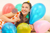 Girl to smile a happy smile with balloons and bonbon — Stock Photo