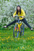 Young woman on green grass with bicycle — Stock Photo