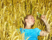 Beautiful smiling girl takes sunbathe in golden field — Stock Photo