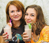 Two beautiful laughing girls drink cocktails with fruits — Stock Photo