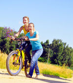 Beautiful smiling girls walk up the hill with bicycle on village — Stock Photo