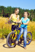 Beautiful smiling girls rest from ride bicycle on village road — Stock Photo