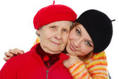 Happy grandmother and granddaughter with berets — Stockfoto