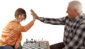 Grandad and granddaughter make a compromise in chess game — Stock Photo