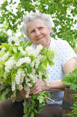 Granny behind bouquet of white flowers — Stock Photo