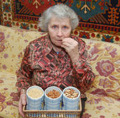 Seventy year old woman sits on sofa and cracks nuts — Stock Photo