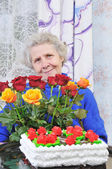 Elderly woman with roses — Stock Photo