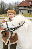 Happy grandmother with white pony — Stock Photo