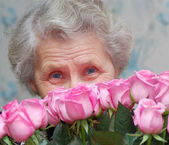 Granny behind bouquet of pink rose — Stock Photo