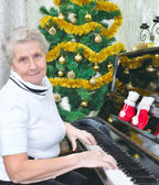 Smiling granny play to piano — Stock Photo