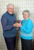 Happy old couple with natural flowers — Stock Photo