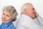 Old happy couple sitting back to back — Stock Photo