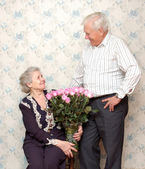 Happy old couple and big bouquet of pink roses — Stockfoto