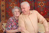 Seventy year old couple smiling at home — Stockfoto