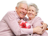 Smiling elderly couple and box with gift — Stockfoto