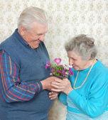 Feliz pareja de ancianos con flores y corazón — Foto de Stock