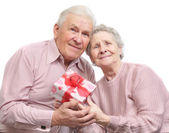Happy old couple and box with gift — Stock Photo