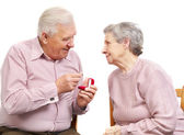Happy old couple with heart-shaped engagement ring — Stock Photo