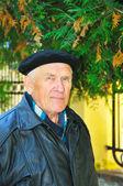 Elderly man on autumn background — Stock Photo