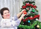 Oudere vrouw siert kerstboom — Stockfoto