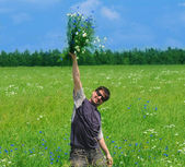 Happy young adult man with bouquet of wildflowers — Stock Photo