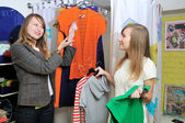 Seller offers to a girl a blouse — Stock Photo
