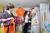Dos hermosas chicas y un hombre compran ropa — Foto de Stock