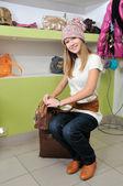 Jovencita en sombrero elegir un bolso — Foto de Stock