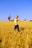 Beautiful girl jumps in golden field — Stock Photo