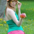 Young girl spectacled and in bonnet with apple — Stock Photo