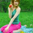 Girl with apple on coverlet — Stock Photo