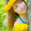 Pretty girl and diadem from yellow dandelions on head — Stock Photo