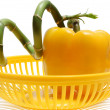 Yellow paprika and green bamboo in yellow basket — Stock Photo