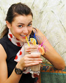Beautiful girl drinks cocktail with sweet fruits — Stock Photo