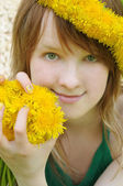 Beautiful girl with red hair and yellow dandelions — Stock Photo