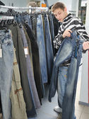 Boy choice jeans in shop — Stock Photo