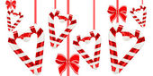 Hearts from candy canes and red bows — Stock Photo